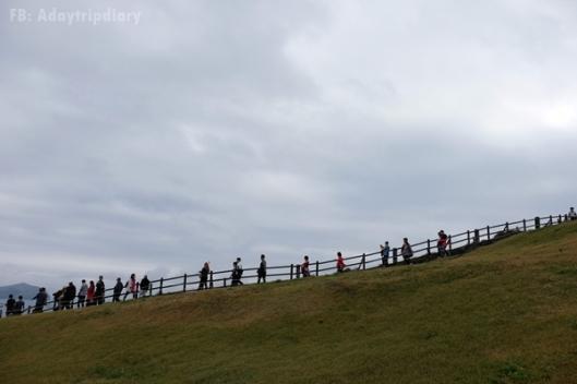 คนเดินเป็นแนวขึ้นไปตามถนนสู่ยอดเครเตอร์ // Seongan Itchulbong peak