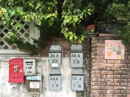 mailboxes in front of a home with beautiful flowers drawing on a door.